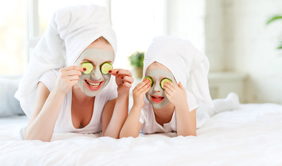 Happy family mother and child daughter make face skin  mask.