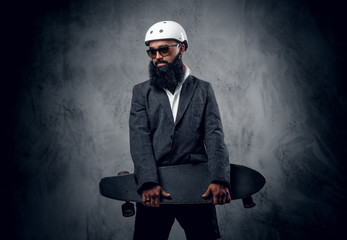 A stylish male dressed in a grey suit holds long board.