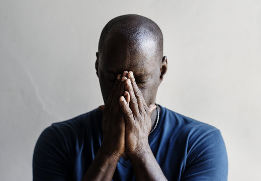 Black man with hands covered his face feeling worried