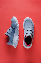 Grey sneakers on pink background. Flat lay and top view