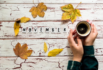"""Above view of incognito woman in green checked shirt holding cup of tea or coffee on old white background, with letters in worlds """" November """" yellow leaves around.Home made decor for autumn season."""