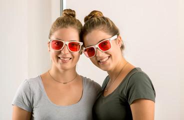 Zwillinge attraktiv und jung lachen mit rosaroten Brillen in die Kamera