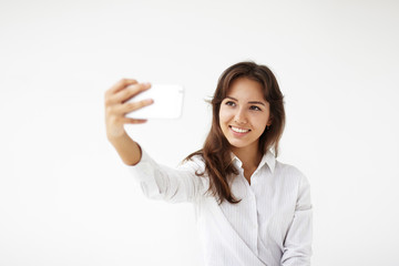Collecting memories. Isolated studio portrait of beautiful charming young mixed-race woman wearing white blouse holding mobile phone in front of her while taking selfie, having happy joyful look