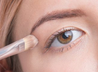 Close up of beautiful young girl applying make up on eyes. Isolated on white