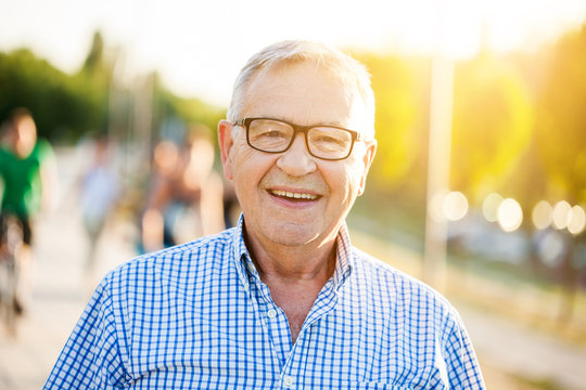 Outdoor portrait of happy senior man who is looking at camera and smiling.