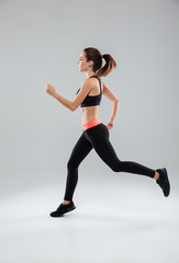 Full length picture of a sports woman running in studio