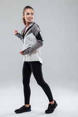 Full length image of happy female runner in warm clothes