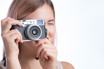 Young stylish girl taking photo with retro camera and looking at camera on white background