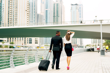 Rear view of attractive stylish couple ready for a trip, walking near the river.