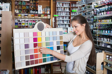 Portrait of young woman holding color sample palette