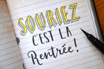 « SOURIEZ, C'EST LA RENTREE » lettrage à la main sur cahier