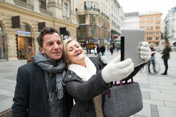 Beautiful senior couple on a walk in city centre taking selfie.