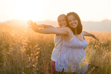 Carefree smiling mother and daughter in the field at sunset