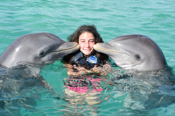dolphin kiss young woman in blue water pool