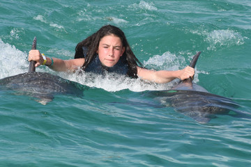 dolphin ride therapy for young woman together in pool