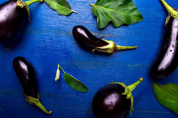 Fresh eggplant background with leaf. Top view. Blue rustic table.