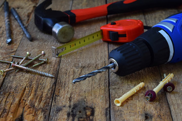 Set of tools for building and treatment on wooden background: hammer, measuring tape, drill