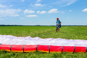 Paragliding instructor waiting with parachute