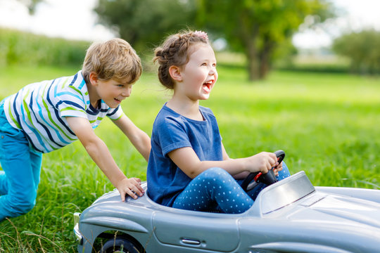 Two happy children boy and girl playing with big old toy car in summer garden, outdoors