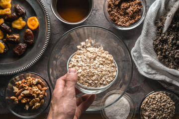 Hand with a bowl of oats and ingredients for the granola
