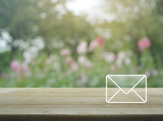 Mail icon on wooden table over blur pink flower and tree, Contact us concept