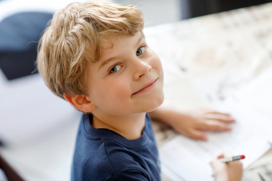Happy smiling kid boy at home making homework writing letters with colorful pens