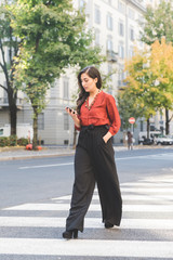 business young woman walking outdoor using smart phone