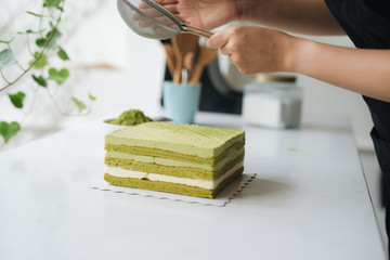 Pour green tea powder over delicious cheesecake
