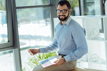 Cheerful young man posing with a laptop on his lap