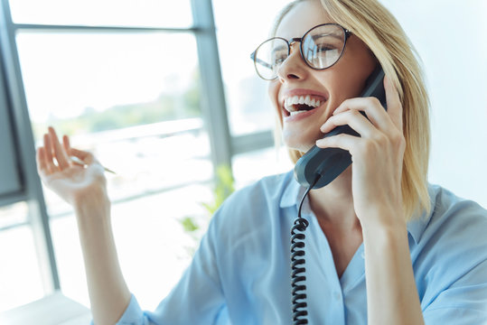 Happy woman laughing while talking on the phone