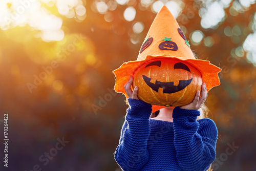 child plays with pumpkin