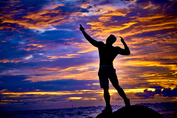 Asian men who stood in the dock of bodybuilders on the beach with a sunset background with beautiful skies.