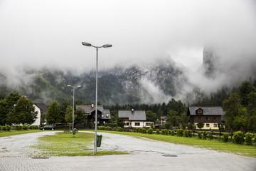 An almost empty parking lot in Hallstatt, Austria, covered in fog