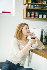 Senior woman drinking red wine in kitchen