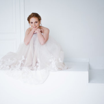Portrait of a beautiful girl in a wedding dress. Bride in luxurious dress sitting on the floor