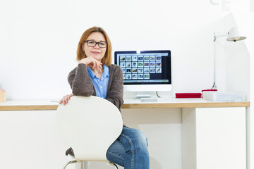 Senior woman sitting at desk with computer monitor