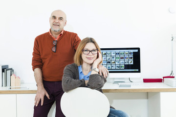 Senior couple at desk with computer monitor at home