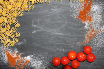 Background with pasta, cherry tomatoes, salt, paprika on chalkboard. Food photo
