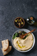 Homemade traditional spread hummus with chopping olives and herbs on blue plate, served with bread, olives variety, olive oil and wood spoon on black texture background. Mediterranean snack. Flat lay