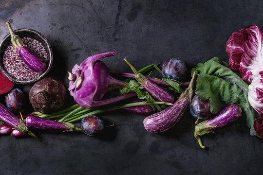 Assortment raw organic of purple vegetables mini eggplants, spring onion, beetroot, radicchio salad, plums, kohlrabi, flower salt over dark metal background. Top view with space