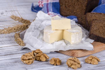 Brie cheese or Camembert cheese. Brie cheese and a slice with walnuts and black bread slice. Italian, French cheese.