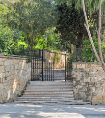 Ascending marble stairs leading to a public park, Stone wall, and fence metal door, Buyukada Island, Istanbul, Turkey