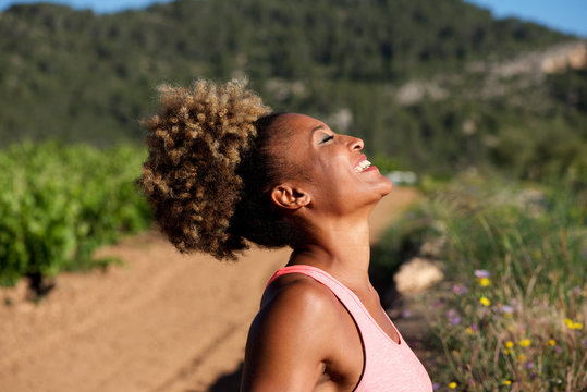 side portrait of healthy young african woman laughing outdoors in morning