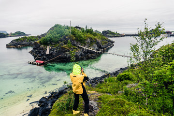 Human photographing a suspension bridge to the island