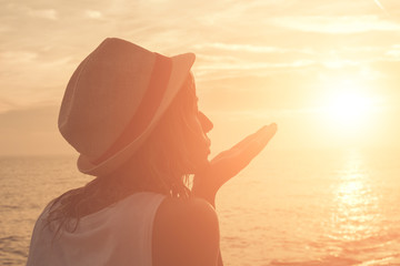 Silhouette of a girl kissing the sun with ocean / sea sunny background.