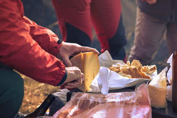 snack in the mountain, man's hand is cutting the food