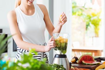 Woman making fruit cocktail