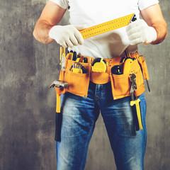 unidentified handyman standing with a tool belt with construction tools and holding roulette against grey background, toned image. DIY tools and manual work concept