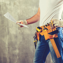 unidentified handyman with hand on waist and tool belt with construction tools holding the project plane against grey background, toned image. DIY tools and manual work concept