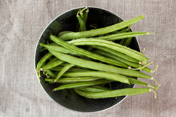 Green beans in a metal bowl on sackcloth